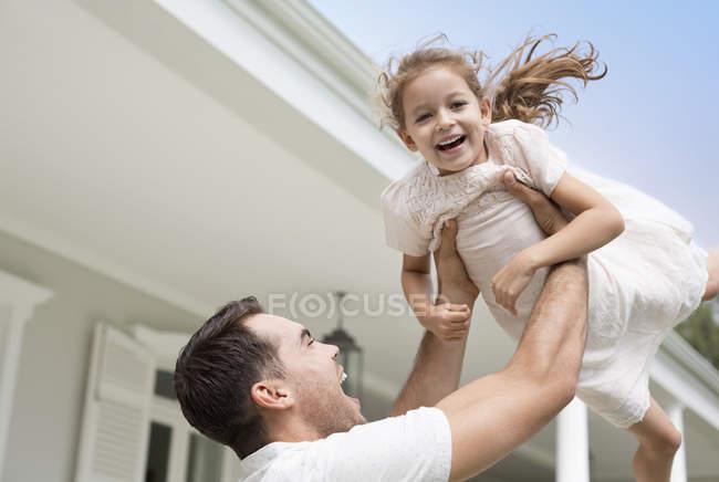 Père et fille jouant hors de la maison — Photo de stock