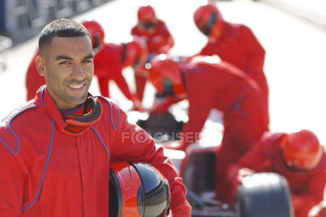Racer standing with team in pit stop — Stock Photo