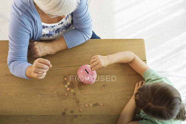 Older woman and granddaughter filling piggy bank — Stockfoto