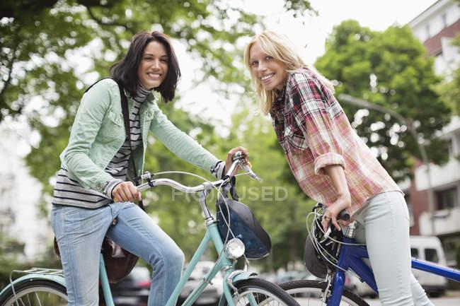 Women sitting on bicycles on city street — Stock Photo