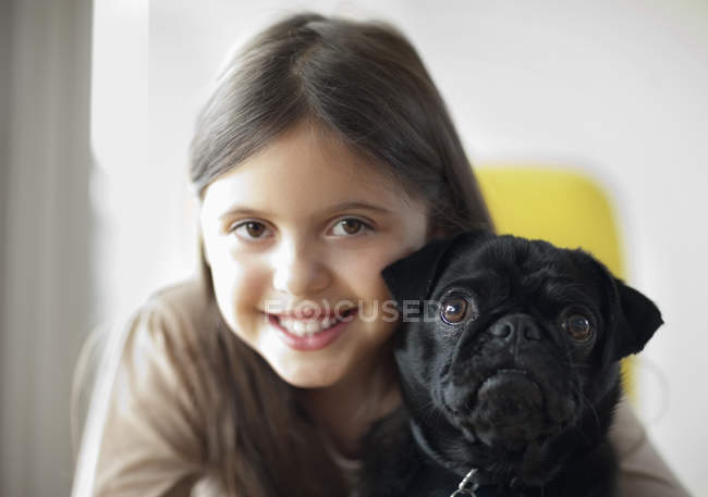 Smiling girl holding dog at modern home — Stock Photo
