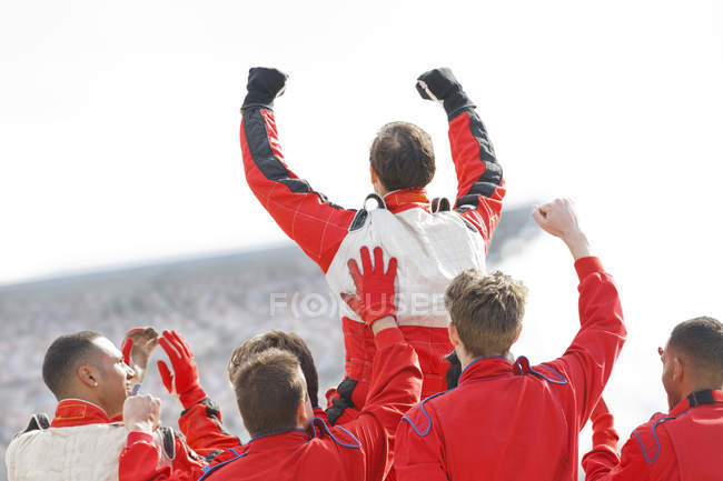 Racer and team cheering on track — Stock Photo