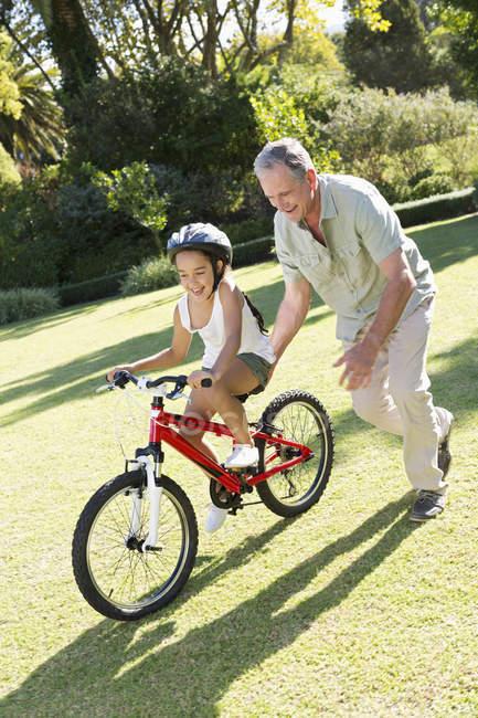 Літня людина викладання внучки, щоб їздити на велосипеді — стокове фото