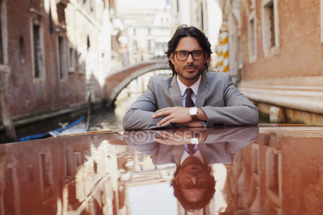 Portrait of serious businessman riding boat in canal in Venice — Stock Photo