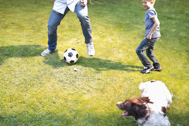 Boy playing soccer with dog outdoors — Stock Photo
