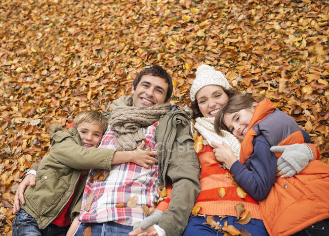 Smiling family laying in autumn leaves — Stock Photo