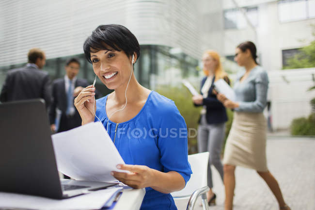 Businesswoman talking on headset at table in office building — Stock Photo