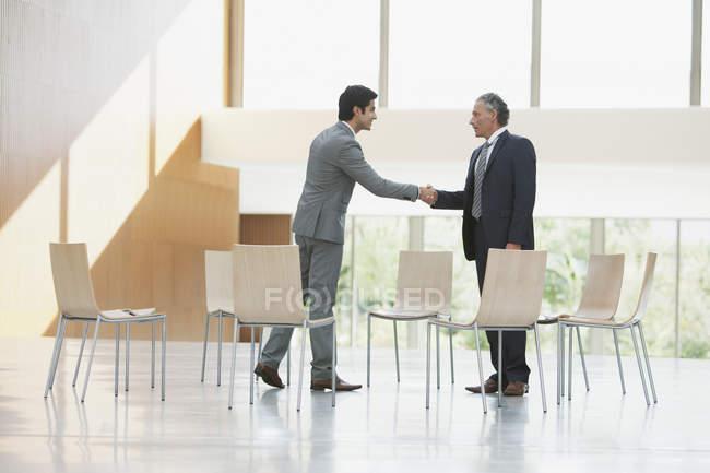 Стулья, окружающие бизнесменов, пожимающие руки — стоковое фото