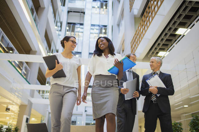 Des gens d'affaires marchent ensemble dans un immeuble de bureaux — Photo de stock
