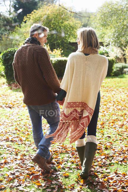 Вид сзади на пару, держащуюся за руки на улице — стоковое фото