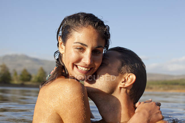 Close up portrait of couple kissing in lake — Stock Photo