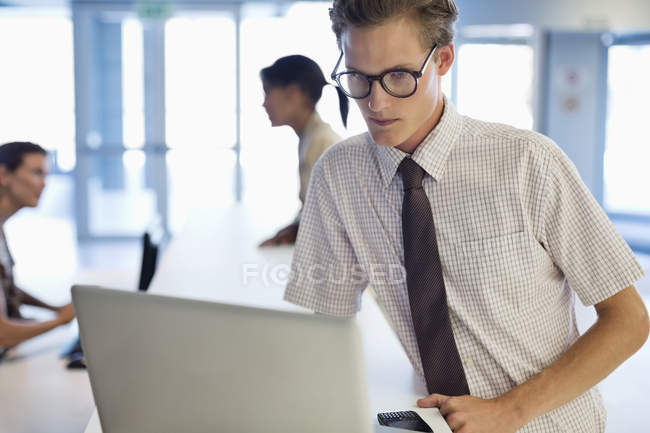 Businessman using laptop at desk at modern office — Stock Photo
