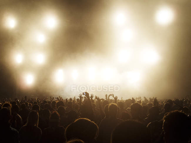 Silhouetted crowd watching illuminated stage at music festival — Stock Photo