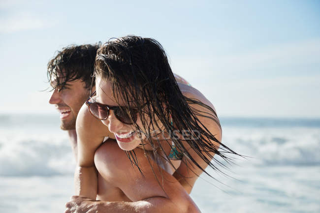 Uomo che trasporta donna entusiasta sulla spiaggia — Foto stock