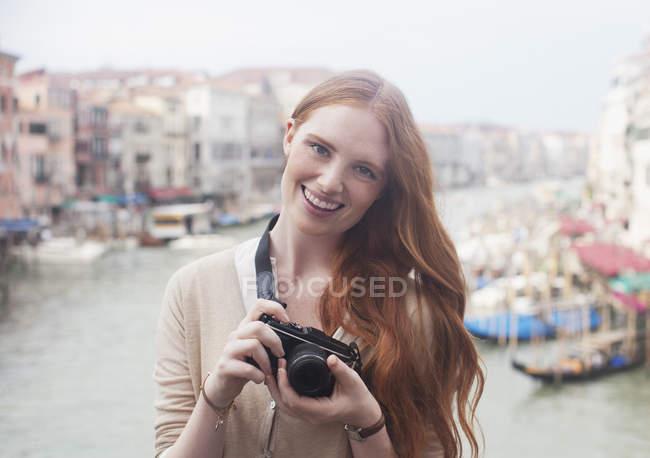 Ritratto di donna sorridente che tiene la macchina fotografica digitale sul lungomare di Venezia — Foto stock