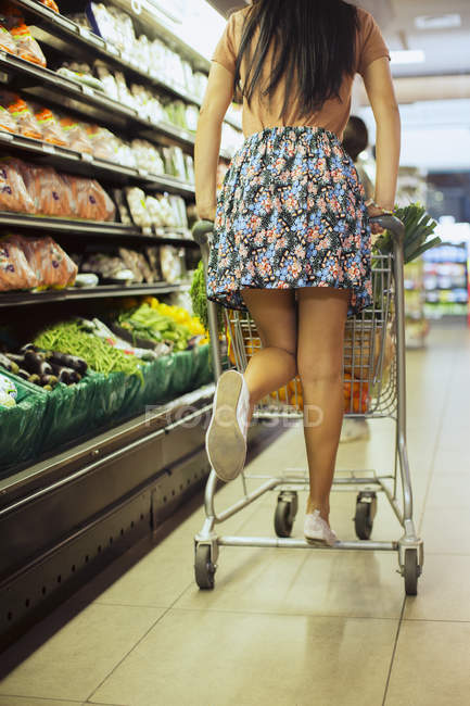Woman playing on shopping cart in grocery store — Stock Photo