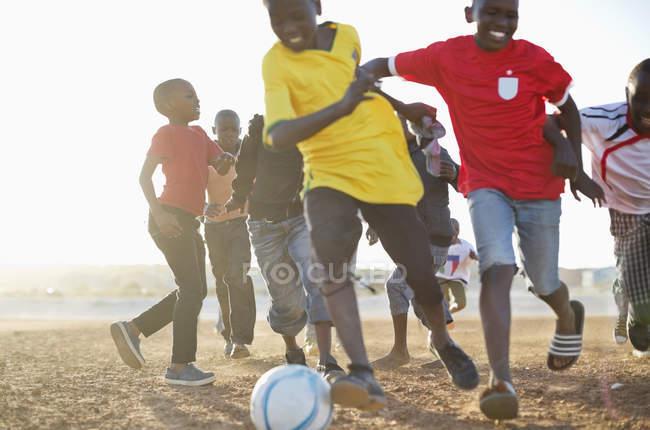 Afrikanische Jungen spielen gemeinsam Fußball auf dem Feld — Stockfoto