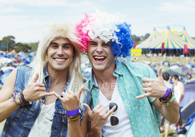 Portrait of men in wigs gesturing at music festival — Stock Photo