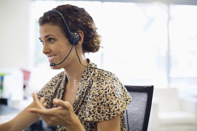 Підприємець говорити на гарнітуру на реєстрації в сучасному офісі — стокове фото