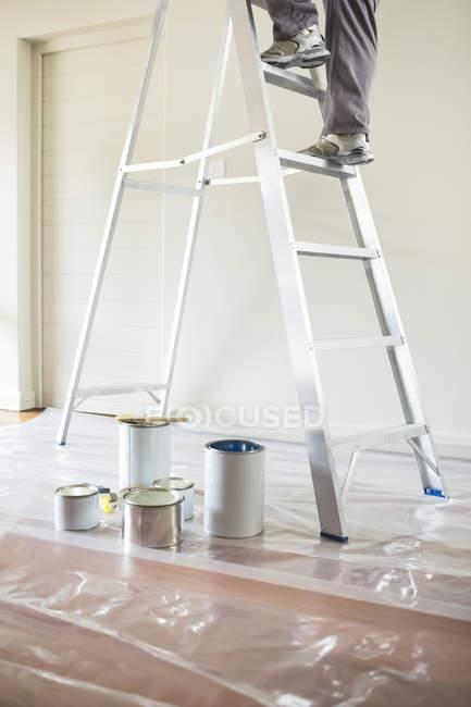 Обрезанный образ человека, взбирающегося по лестнице в комнату для покраски — стоковое фото