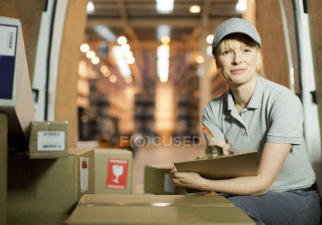 Delivery girl checking boxes in van — Stock Photo