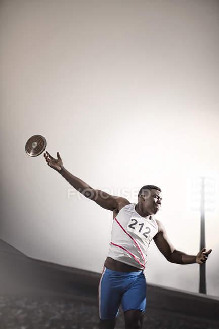 Pista y campo atleta lanza disco - foto de stock