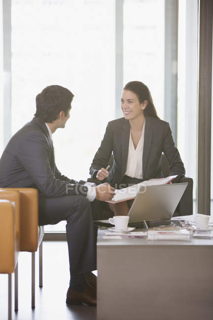 Smiling businessman and businesswoman reviewing paperwork — Stock Photo
