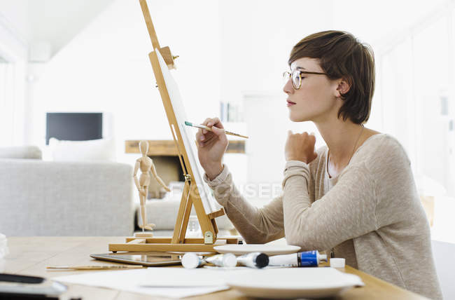 Woman painting on easel at table — Stock Photo