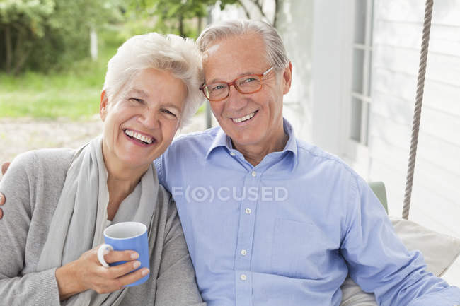 Smiling couple sitting on porch swing — Stock Photo