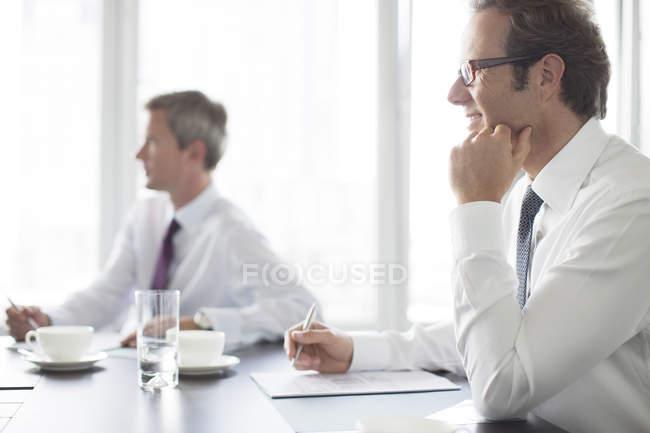 Uomini d'affari seduti in riunione presso l'ufficio moderno — Foto stock