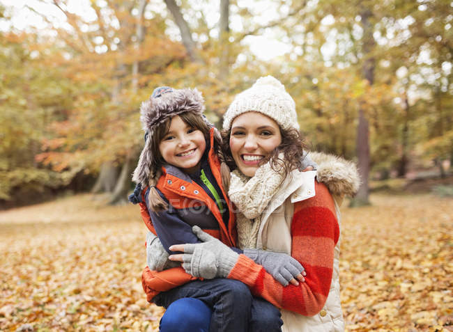Mother and daughter smiling in autumn leaves — Stock Photo