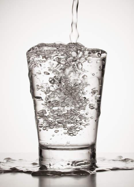 Вода б'є через край зі скла — стокове фото