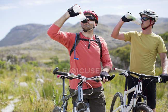 Горные велосипедисты за рулем воды в сельской местности — стоковое фото