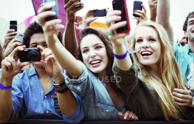 Aficionados con cámaras y teléfonos con cámara en el festival de música - foto de stock