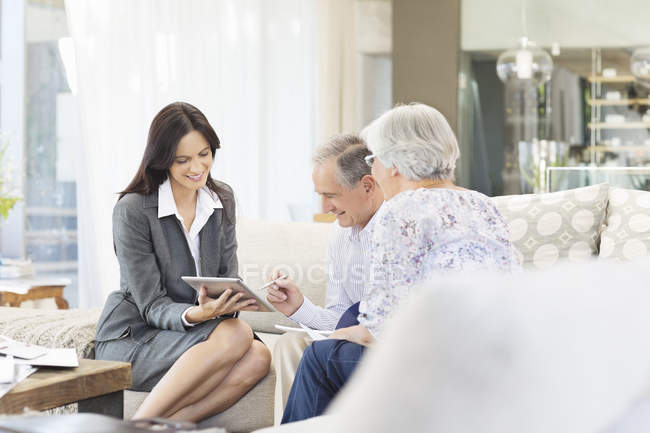 Financial advisor using tablet computer with clients — Stock Photo