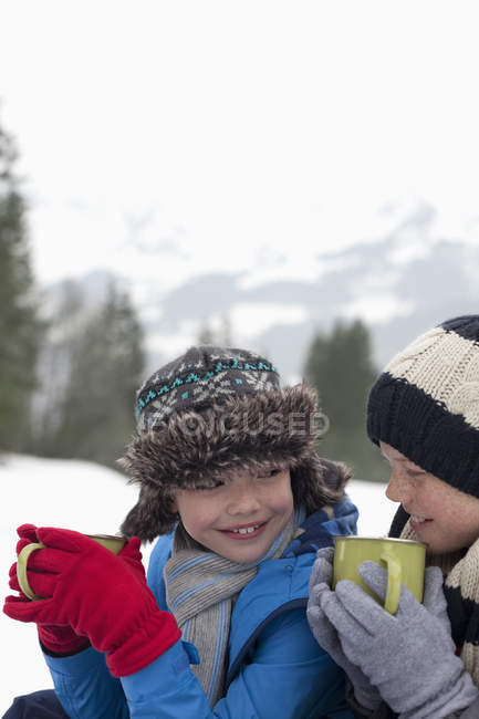 Close up of happy boys drinking hot chocolate in snowy field — Stock Photo