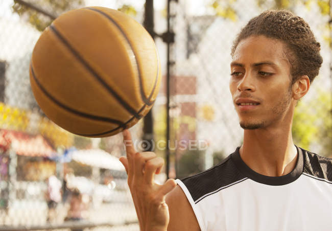Man spinning basketball on finger t court — Stock Photo