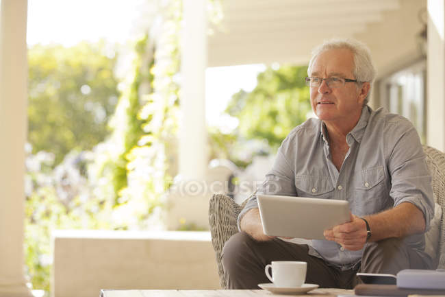 Smiling man using digital tablet on porch — Stock Photo