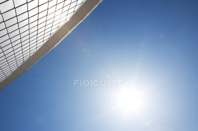 Sun by modern building in blue sky — Stock Photo
