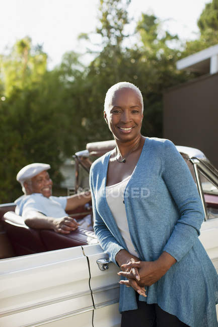 Smiling older woman leaning on convertible — Stock Photo