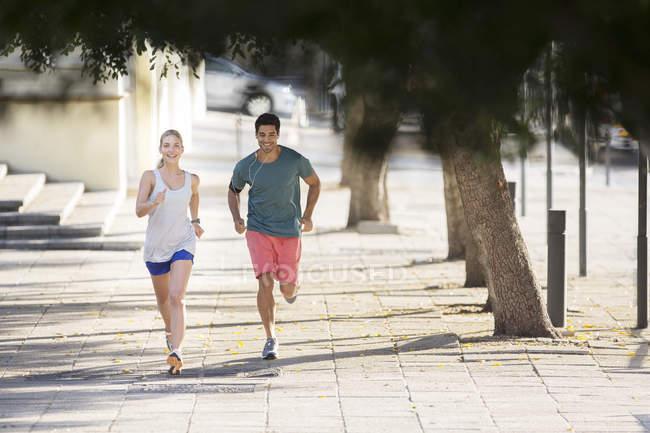 Pareja corriendo por las calles de la ciudad juntos - foto de stock