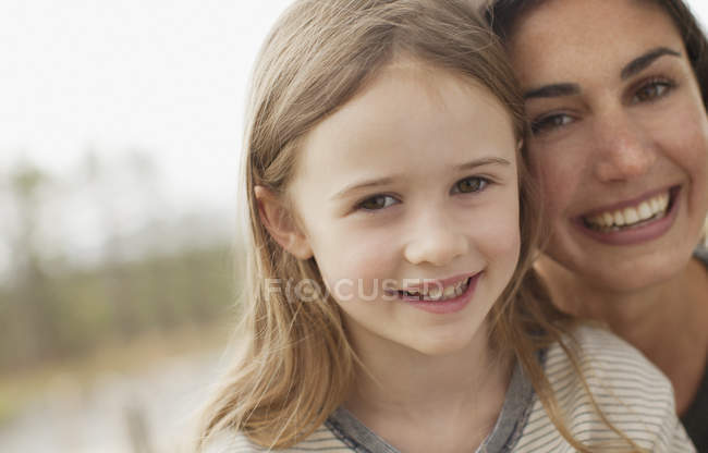 Close up portrait of smiling mother and daughter — Stock Photo