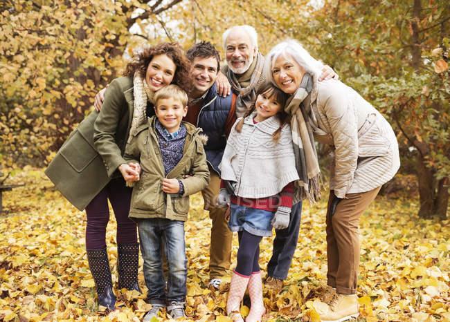 Familia feliz sonriendo juntos en el parque - foto de stock