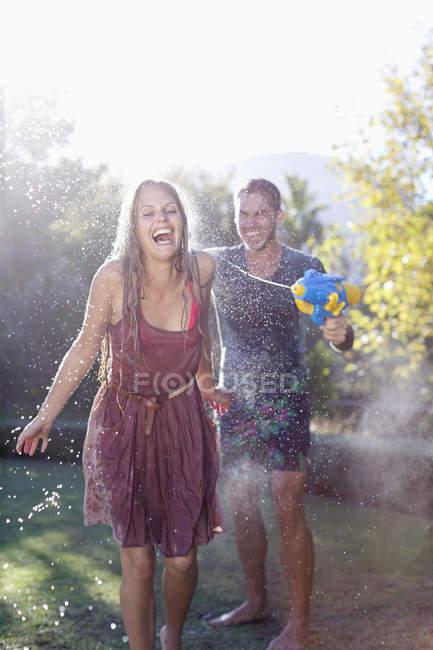 Coppia che gioca con pistole ad acqua in cortile — Foto stock