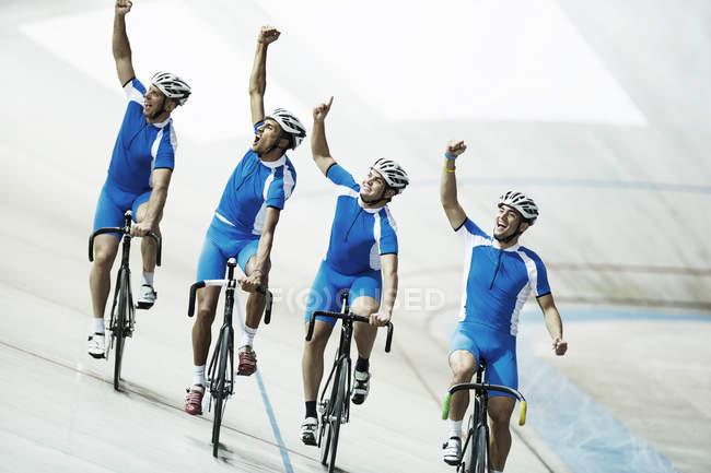 Команда велосипедистов на велодроме с поднятыми руками — стоковое фото