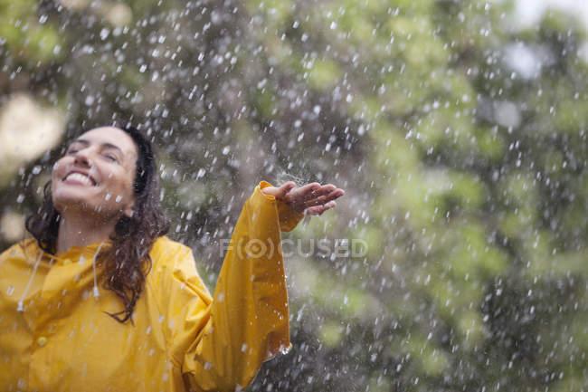 Счастливая женщина, стоящая с распростертыми руками под дождем — стоковое фото