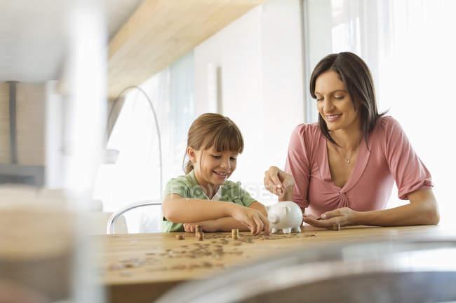 Madre e figlia riempimento piggy bank — Foto stock