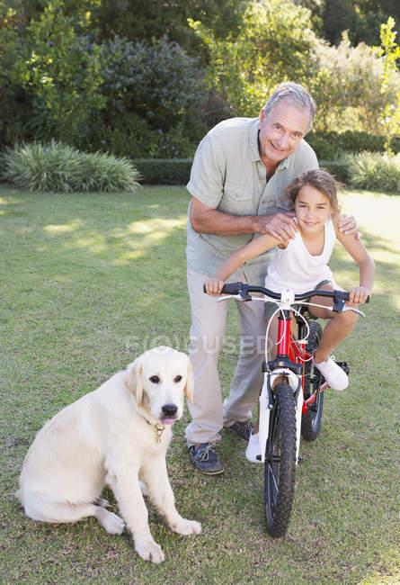 Пожилой мужчина с внучкой и собакой — стоковое фото