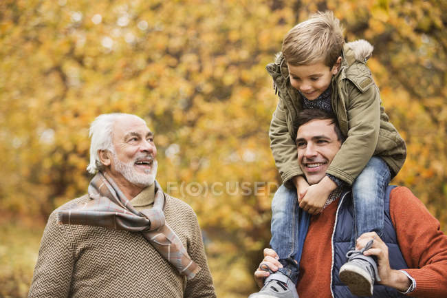 Three generations of men smiling in park — Stock Photo