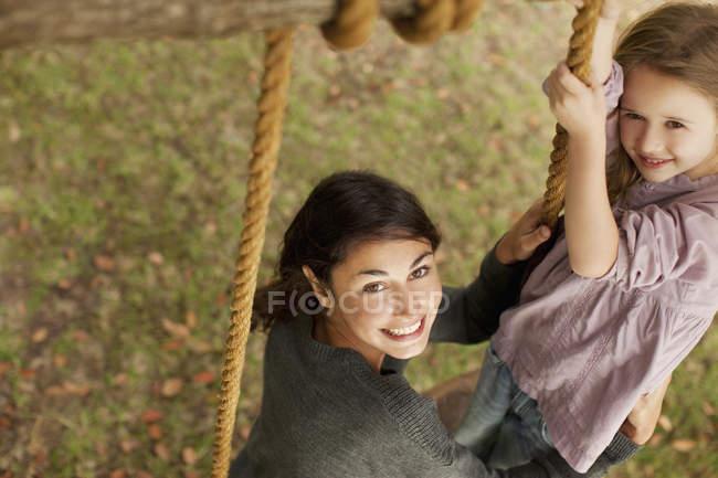 Портрет улыбающейся матери и дочери на качелях — стоковое фото